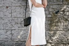 a white straight spaghetti strap midi dress with side slits, a black bag and grey trainers