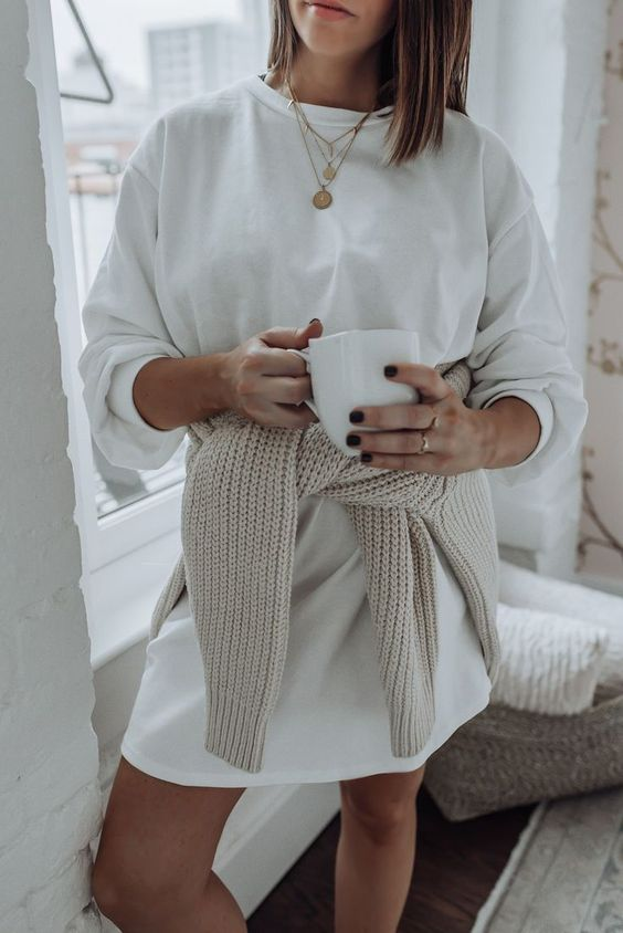 a white sweatshirt over the knee dress paired with layered necklaces and with a chunky knit sweater for a colder day