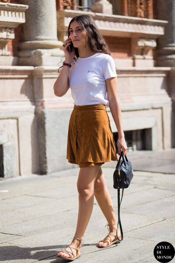 a white tee, an amber suede mini skirt, tan Greek sandals and a small bag for a casual summer look