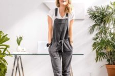 a white tee and a grey overalls with pockets make up a nice outfit for a casual day at home