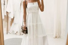 a white tiered A-line midi dress of linen or cotton, red Greek sandals and a comfy bag