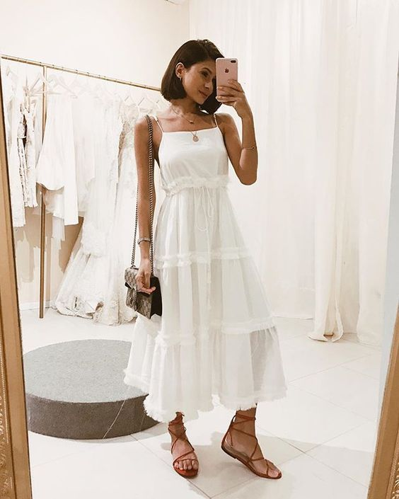 a white tiered A line midi dress of linen or cotton, red Greek sandals and a comfy bag