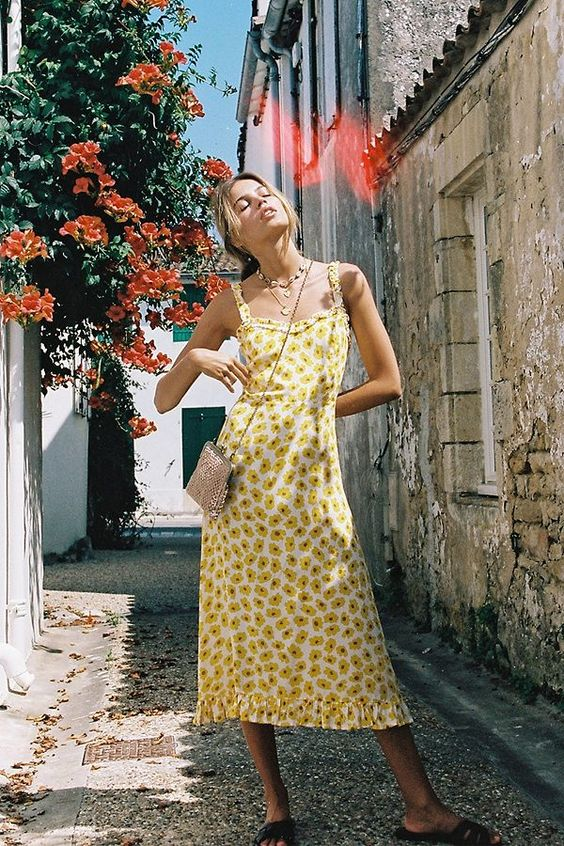a yellow A-line floral midi dress with straps and a ruffle skirt, a mini bag, slippers and seashell accessories