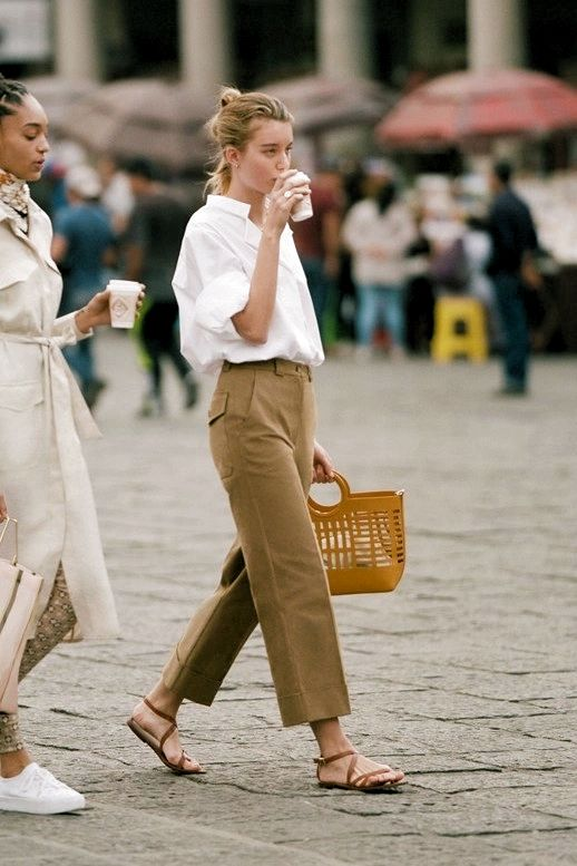 an oversized white shirt, tan cropped pants, brown Greek sandals and a comfy bag for work