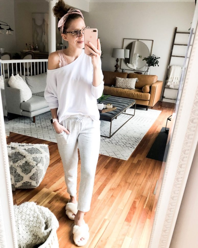 grey joggers, a white one shoulder top, a pink lace bralette and fluffy slippers for more comfort