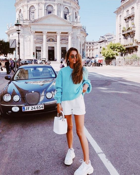 a blue sweater, white mini shorts, white trainers and a white bucket bag for a spring to summer look or a summer to fall one
