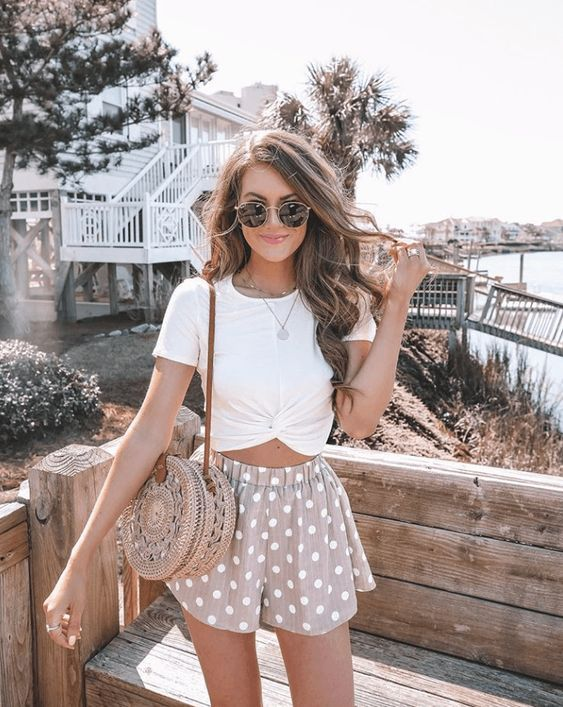 a romantic look with a draped white tee, blush polka dot mini shorts, a woven round bag for summer