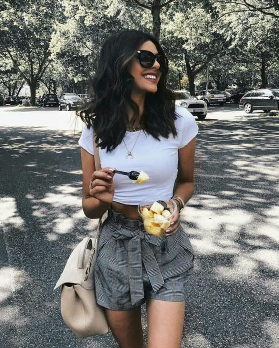 a white crop top, grey plaid mini shorts, a large neutral bag for a cute casual summer look
