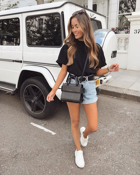 a modern summer look with a black oversized tee, blue denim shorts, white sneakers and a black crossbody