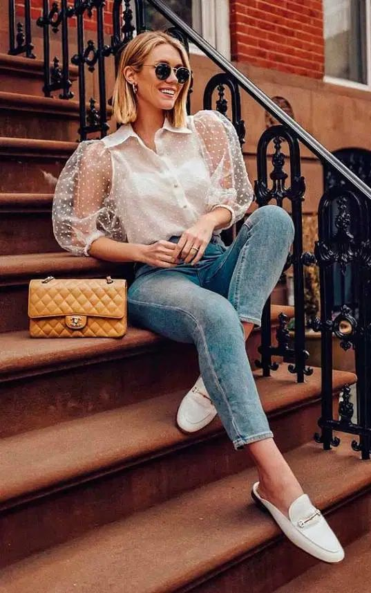 a stylish outfit with blue cropped skinnies, a white sheer sleeve blouse, white mules, a yellow bag