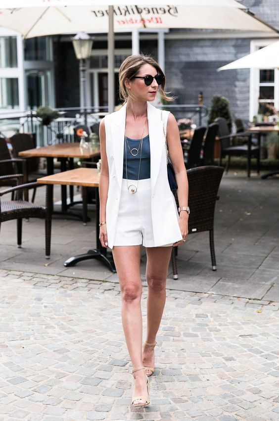 a chic summer look with a white waistcoat, a graphite grey top, white mini shorts, tan heels and layered necklaces