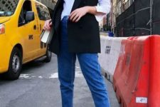 13 a white shirt, blue cuffed jeans, a black waistcoat, black sneakers and a white bag