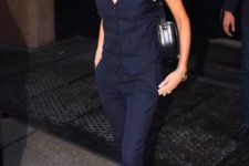 15 Victoria Beckham wearing a navy pin stripe suit with skinny pants and a waistcoat, black shoes and a bag