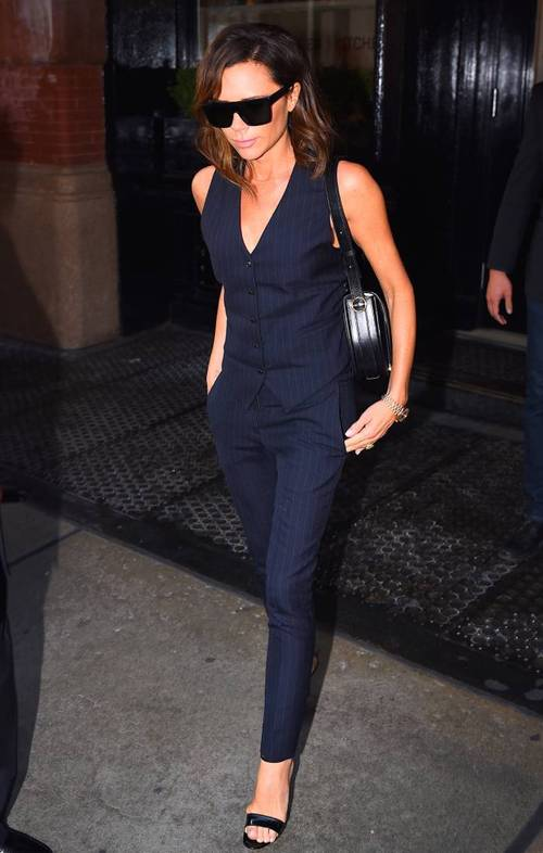 Victoria Beckham wearing a navy pin stripe suit with skinny pants and a waistcoat, black shoes and a bag