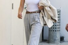 Rosie Huntington-Whiteley wearign a white halter top, grey pleated pants, mesh heels and a neutral blazer