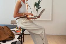 Rosie Huntington Whiteley wearing a white halter top, neutral wideleg pants, tan square toe heels