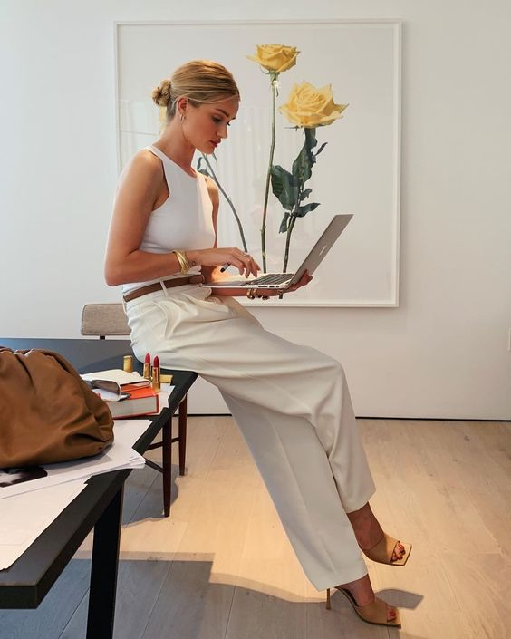 Rosie Huntington Whiteley wearing a white halter top, neutral wideleg pants, tan square toe heels