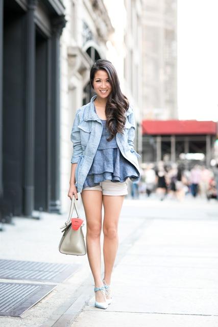 With beige shorts, light blue jacket, beige bag and light blue high heels