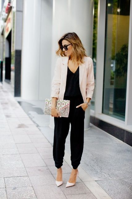 With black jumpsuit, printed clutch and beige pumps
