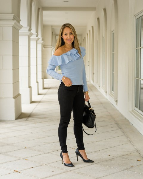 With black skinny pants, black bag and pumps