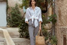 With checked high-waisted pants, straw bag and brown sandals