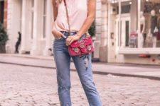 With distressed cuffed jeans, red embellished bag and beige pumps