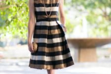 With golden clutch, necklace and black pumps