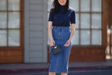 With navy blue turtleneck, black mini bag and gray mules