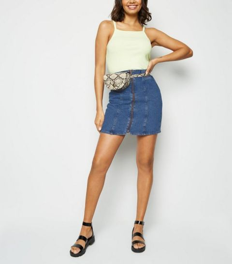 With pastel colored top, snake printed waist bag and black flat sandals