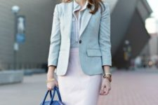 With striped button down shirt, white knee-length skirt and blue bag