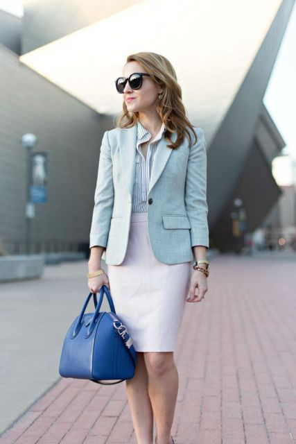 With striped button down shirt, white knee length skirt and blue bag