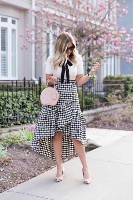 With white and black blouse, pale pink bag and high heels