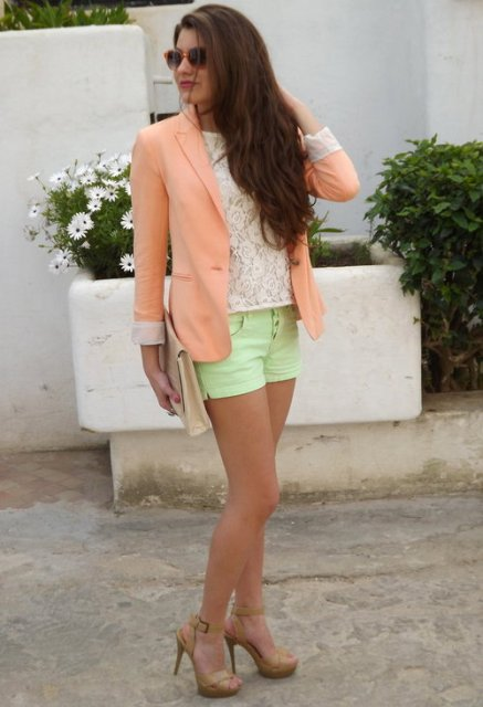With white lace shirt, green shorts, beige clutch and beige shoes