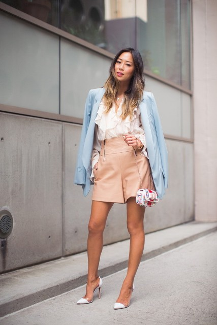 With white ruffled blouse, beige high waisted shorts, printed mini bag and white high heels