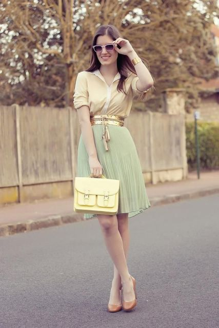With yellow shirt, mint green pleated skirt, golden belt and brown shoes