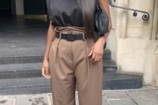 a black padded shoulder top, taupe high waist pants, shiny shoes and a black bag for a statement look