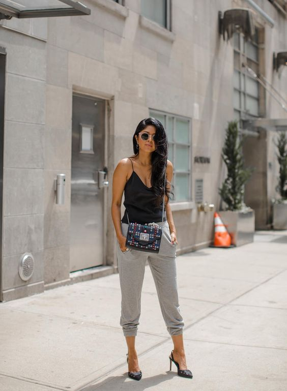 a black spaghetti strap top, grey joggers, black studded slingbacks and a colorful crossbody bag