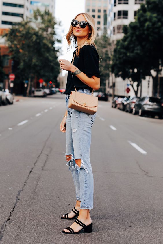 a black tee, blue ripped jeans, a blush crossbody bag and black strappy mules with block heels