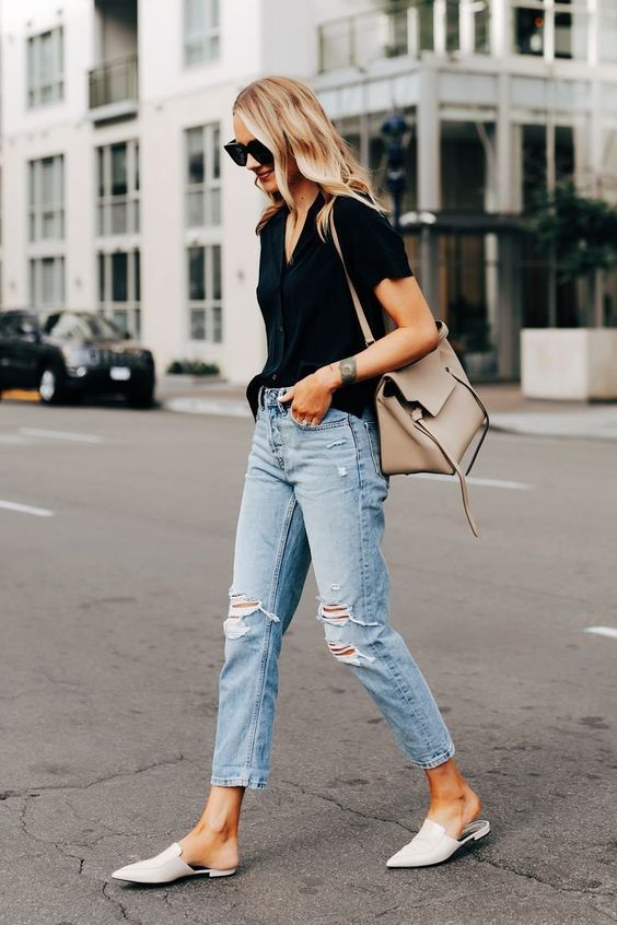 a black tee, blue ripped jeans, white pointed toe mules and a neutral tote for work