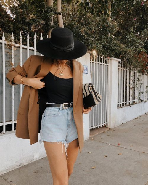 a black top, blue denim shorts, an oversized tan blazer, a black hat for a statement look