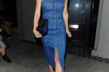 a blue button up denim midi dress with a front slit, a dark clutch and brown heels