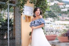 a blue ruffle off the shoulder top, a white pleated midi, nude block heels and a neutral bag
