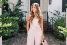 a blush jumpsuit with no sleeves and wideleg pants, a blush bag and matching heeled mules for work