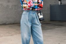 a bold and trendy look with a colorful short, baggy jeans, black heels and tassel earrings