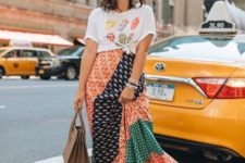 a bright printed t-shirt, a multi printed midi skirt, white slippers and a tan bag