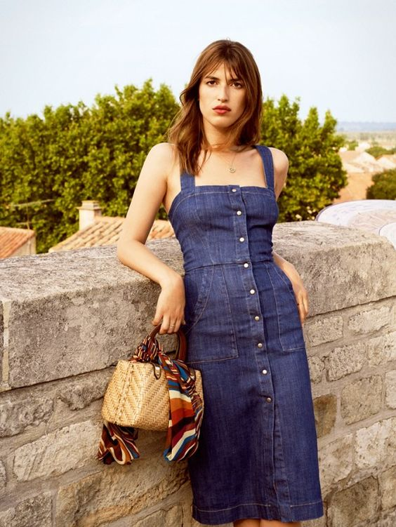 a button down denim dress is worn with a necklace and straw structured bag
