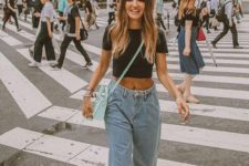a casual look with a black crop t-shirt, blue baggy jeans, black Greek sandals and a mint bag