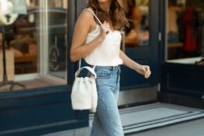 a casual look with a white lingerie top, blue jeans, a white bucket bag and tan strappy block heels