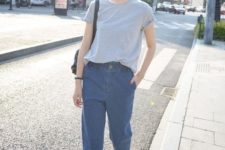 a casual outfit with a grey tee, blue baggy jeans, white sneakers and a black bag