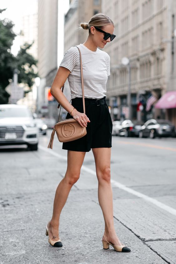 a casual outfit with a striped tee, black shorts, two tone slingbacks, a nude crossbody and a low bun